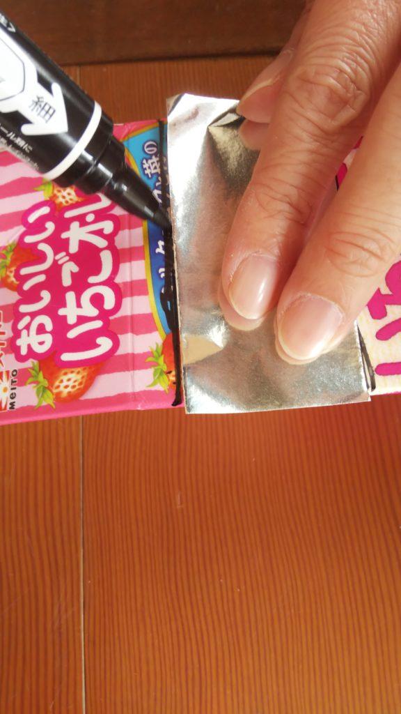 切った折り紙の1枚の幅に牛乳パックに印をつけて切る